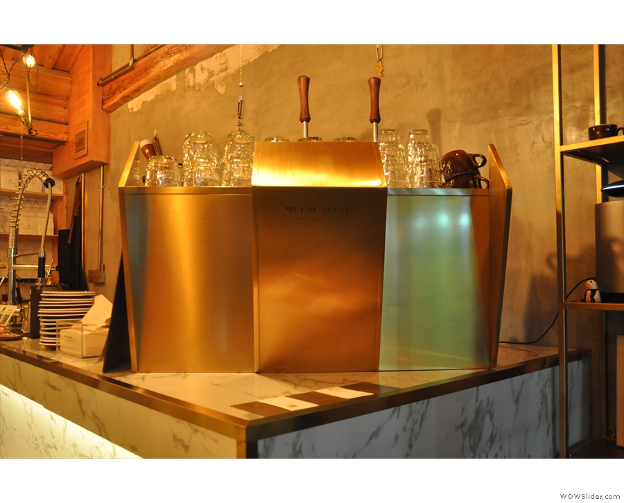Stepping inside, you're immediately greeted by the gleaming metal espresso machine...