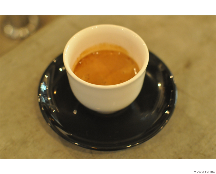 An interesting twist; classic black saucer, but white, handless cup.