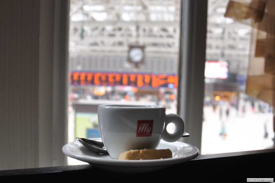 My espresso, keeping a (blurry) eye on the trains for me