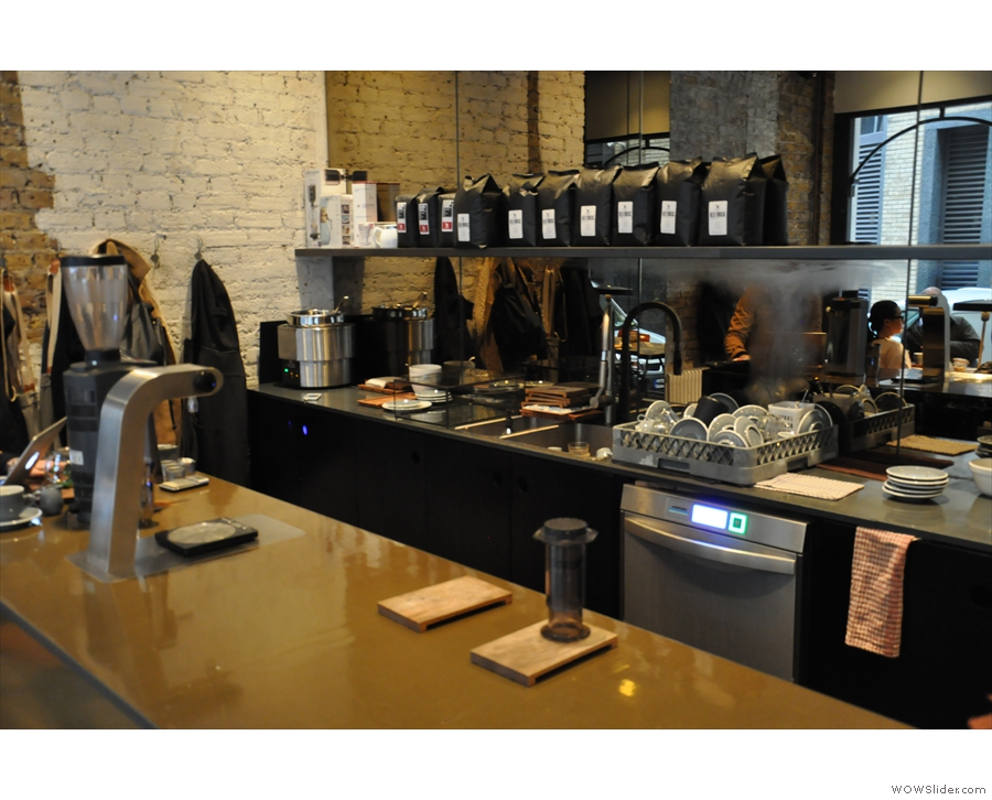 The counter is sparsely populated. The brew bar, with its own grinder, is at the far end.