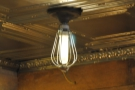 ... a bare bulb hangs from the tin ceiling.