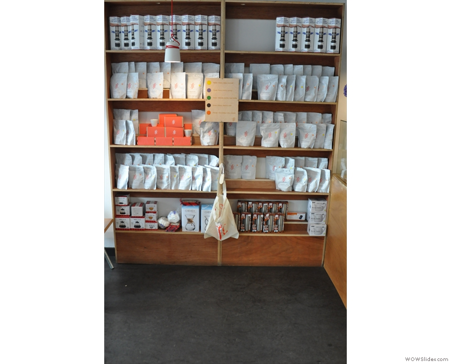 There's this set of shelves to the left of the counter, full of beans and coffee kit.