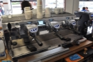 A behind-the-scenes view of the Black Eagle, with a Nuova Simonelli grinder to the right.