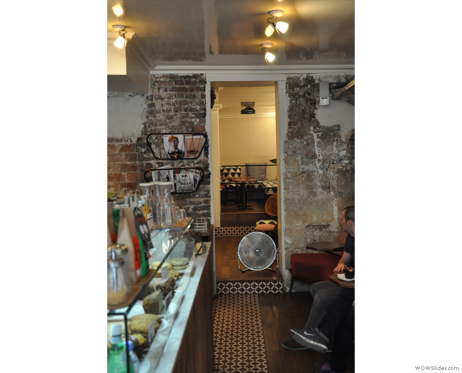 Beyond the counter, a narrow doorway leads to more seating.