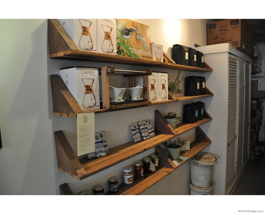 Shelves of coffee and coffee-making kit for sale at the back.