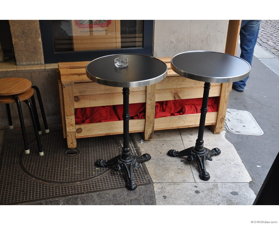 These two tables are between the street and the door. I like the bench.