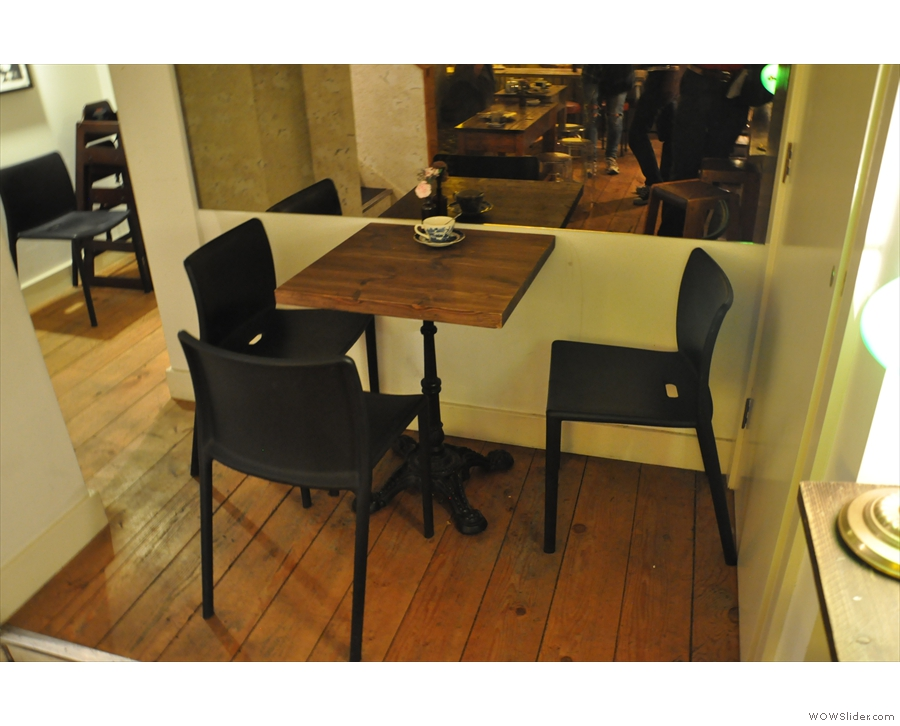 There's this three-person table on a slghtly raised platform at the bottom of the stairs...