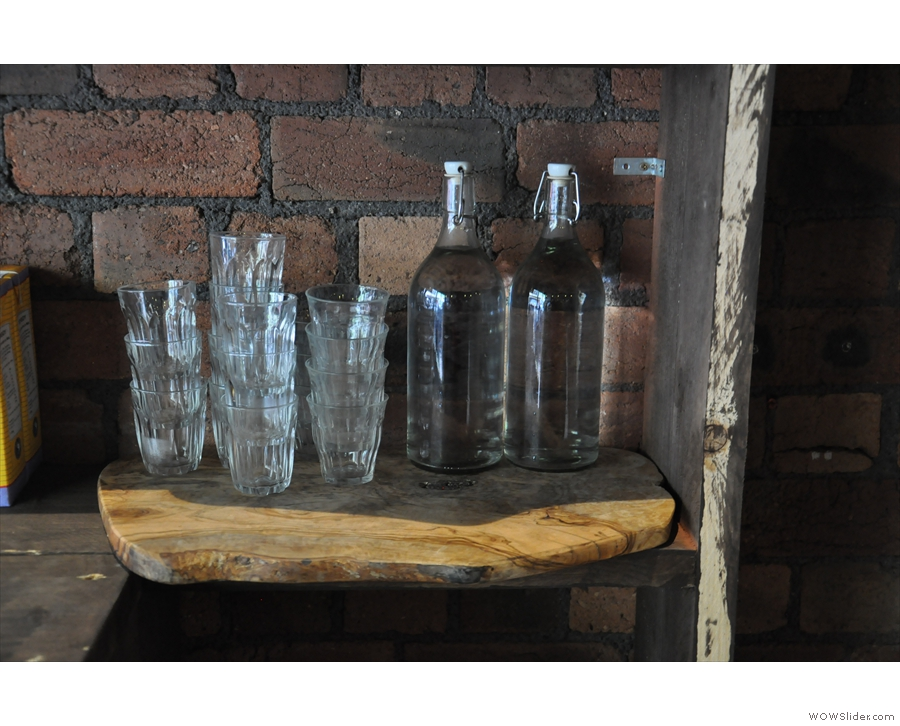 A neat little shelf with bottles of water for you to take to your table.