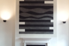At the other end of the room, there's another fireplace, abstract art on the chimney-breast.