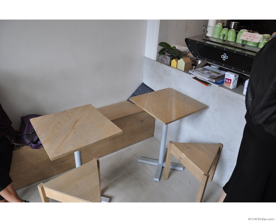 Some of the tables and the triangular stools along the bench on the left-hand wall.