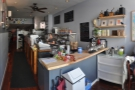 A panoramic view from just inside the door. The front is dominated by the counter...