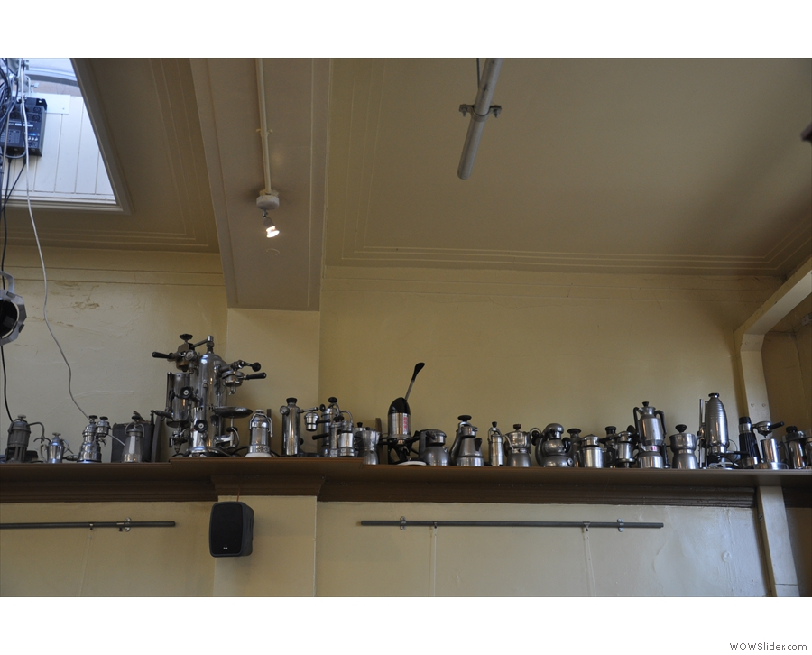 There's a shelf opposite the counter with lots of old coffee-making kit...