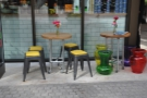 Some more of outdoor seating: a pair of tables (on wheels) to the right of the door.