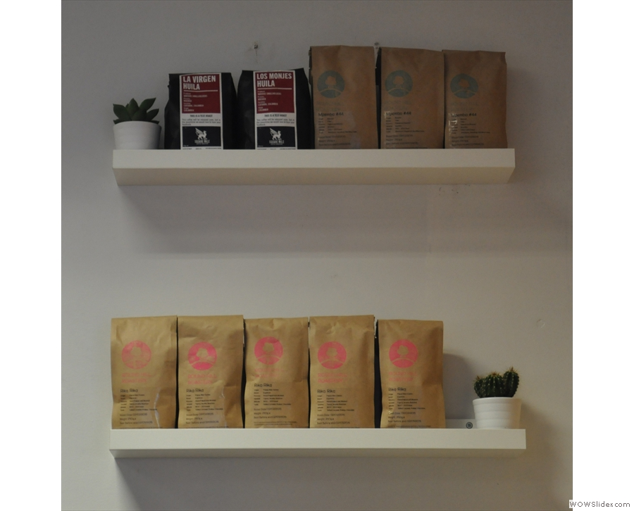 Bags of coffee for sale on shelves behind the counter...