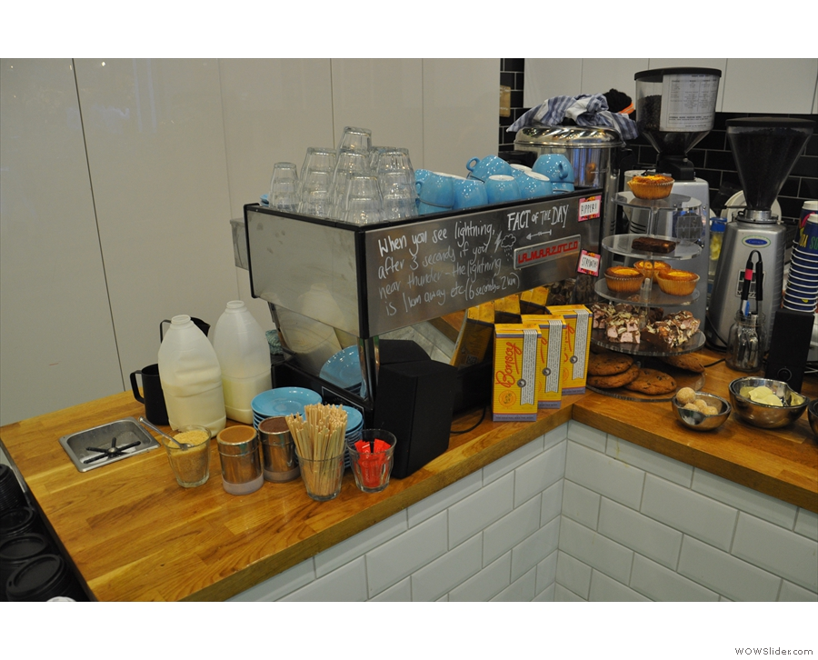 The espresso machine is at the far end of the counter, facing the door.