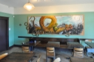 A panoramic view of the pew, with its tables and the amazing dragon painting on the wall.