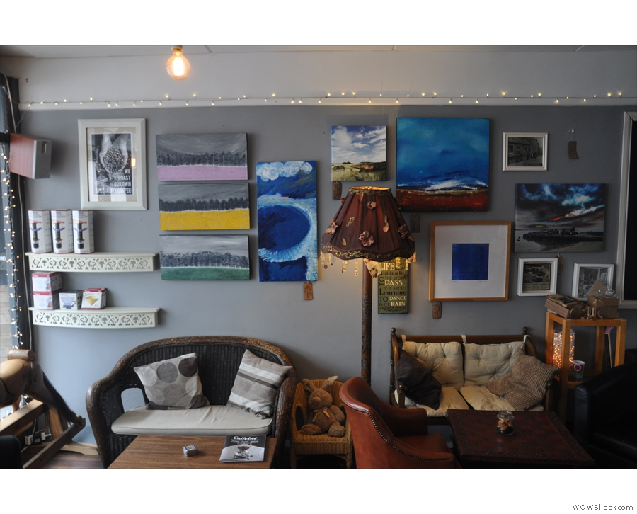 Both walls are adorned with an eclectic range of works of art, including paintings & photos.