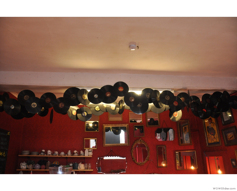 Old vinyl records hang from the ceiling in front of the wall, itself adorned with mirrors.