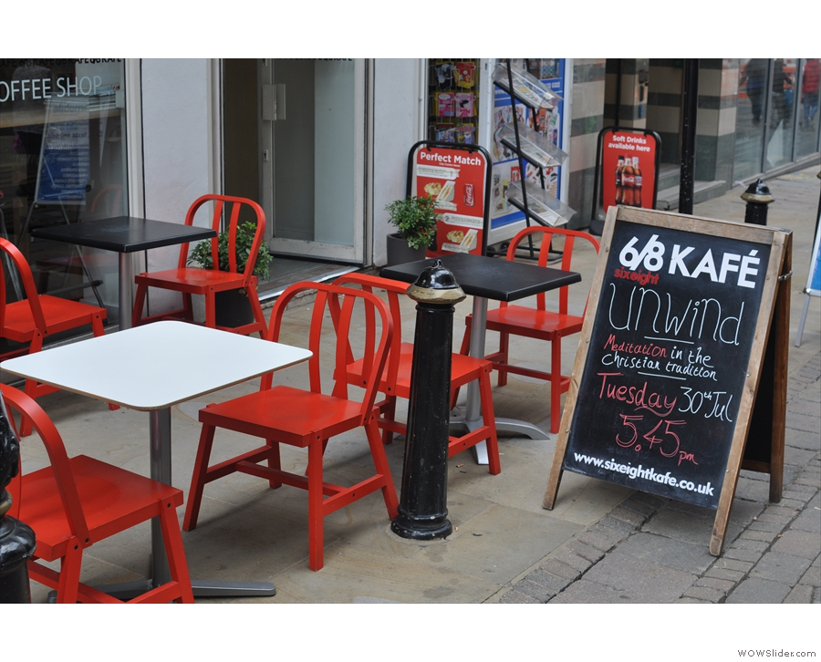 Four tables on the pavement outside provide one seating option.