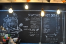 The menu is chalked up on the wall behind the counter.