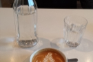 My flat white, complete with complimentary bottle of water: the joys of table service.