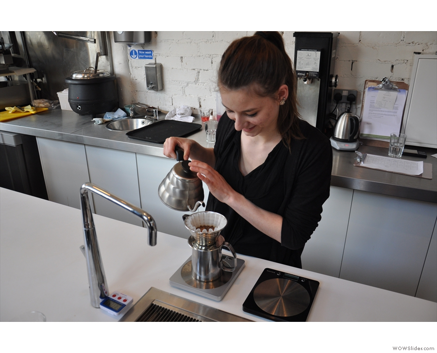 After putting the coffee into the Kalita Wave filter, she adds hot water.