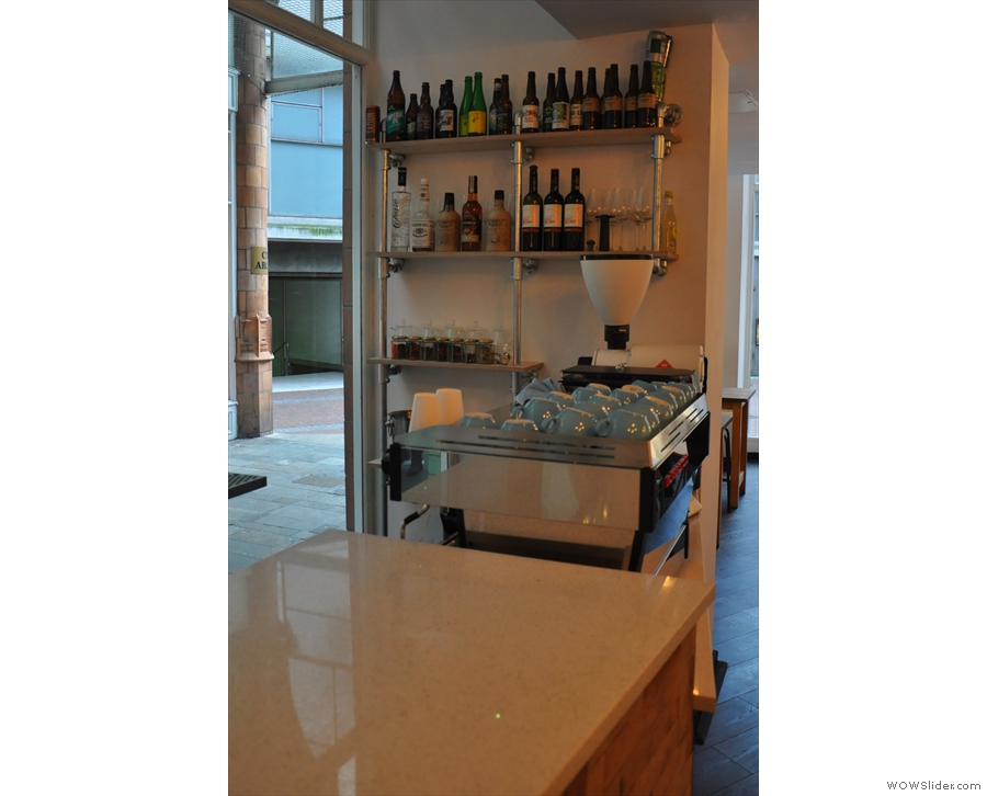 The bottled beer, wine and spirits are on shelves by the espresso machine...