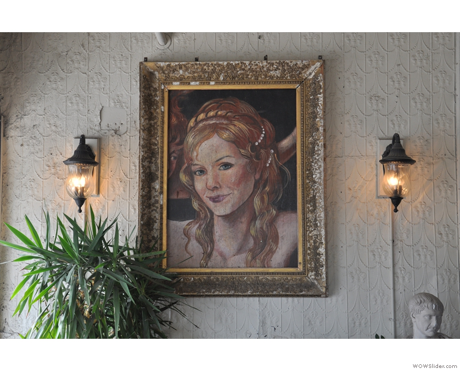 This fascinating portrait hangs above the comfy seating to the left as you come in.