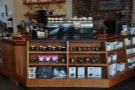 There are retail shelves in the front of the counter, selling merchandising and coffee-kit.