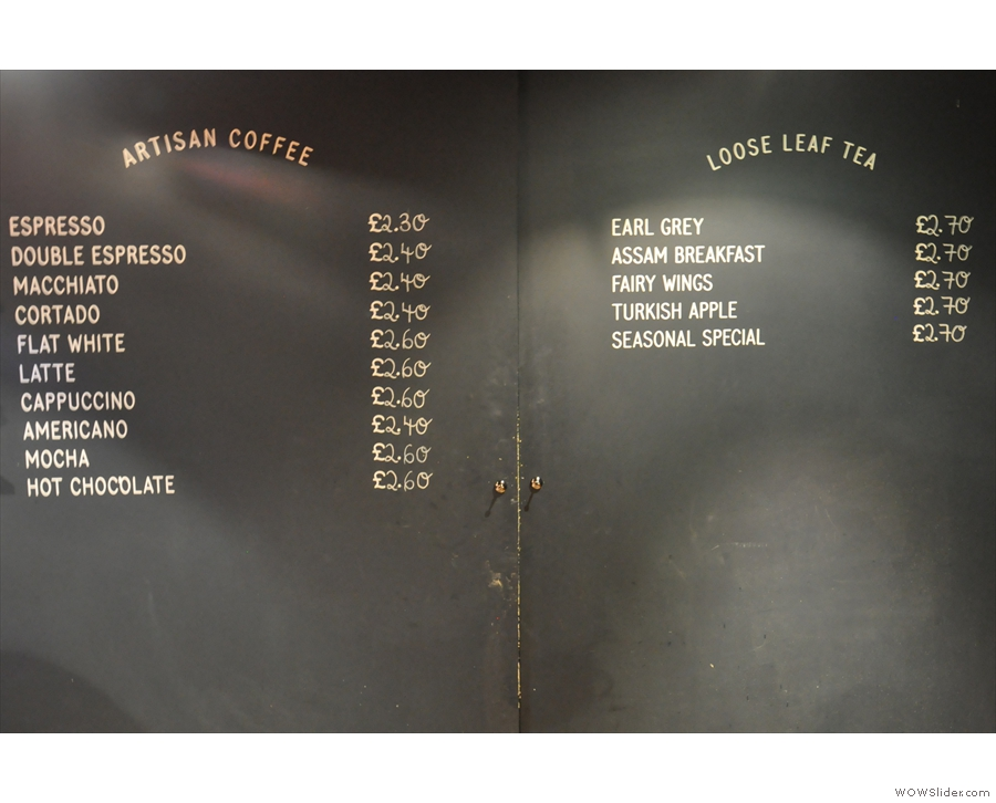 The hot drinks are printed on the wall behind the counter...