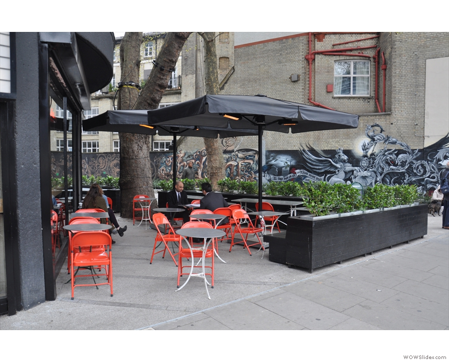 There's plenty of outdoor seating, including this area, fenced off by planters on the right.