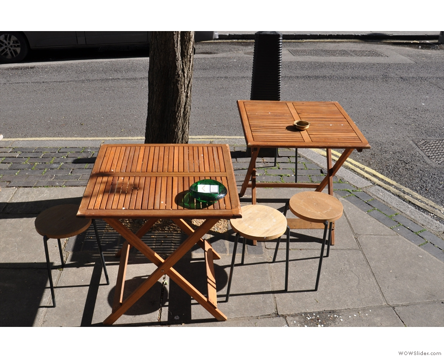 There are more tables outside on the other side of the pavement, under a tree.