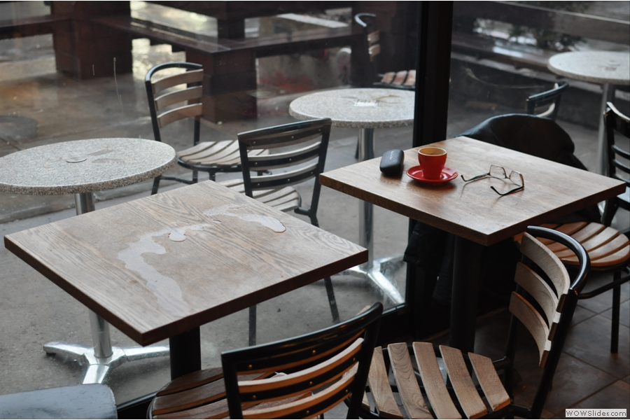 I failed miserably to get any decent interior shots. Here is a picture of a couple of tables by the windows, complete with Jovan the Poet's glasses.
