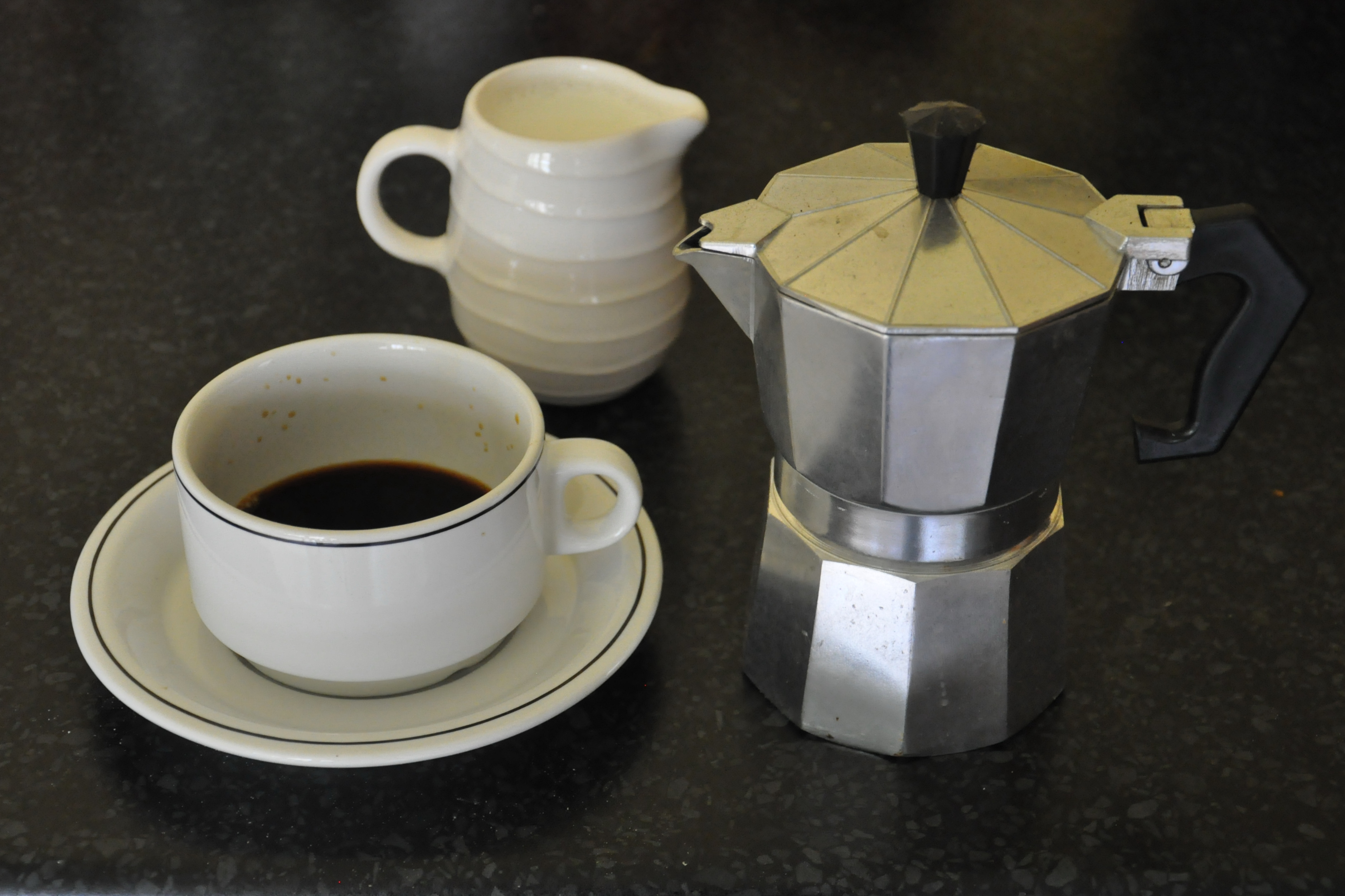A cup of coffee, poured from a stove-top espresso machine with a pot of warm milk in the background