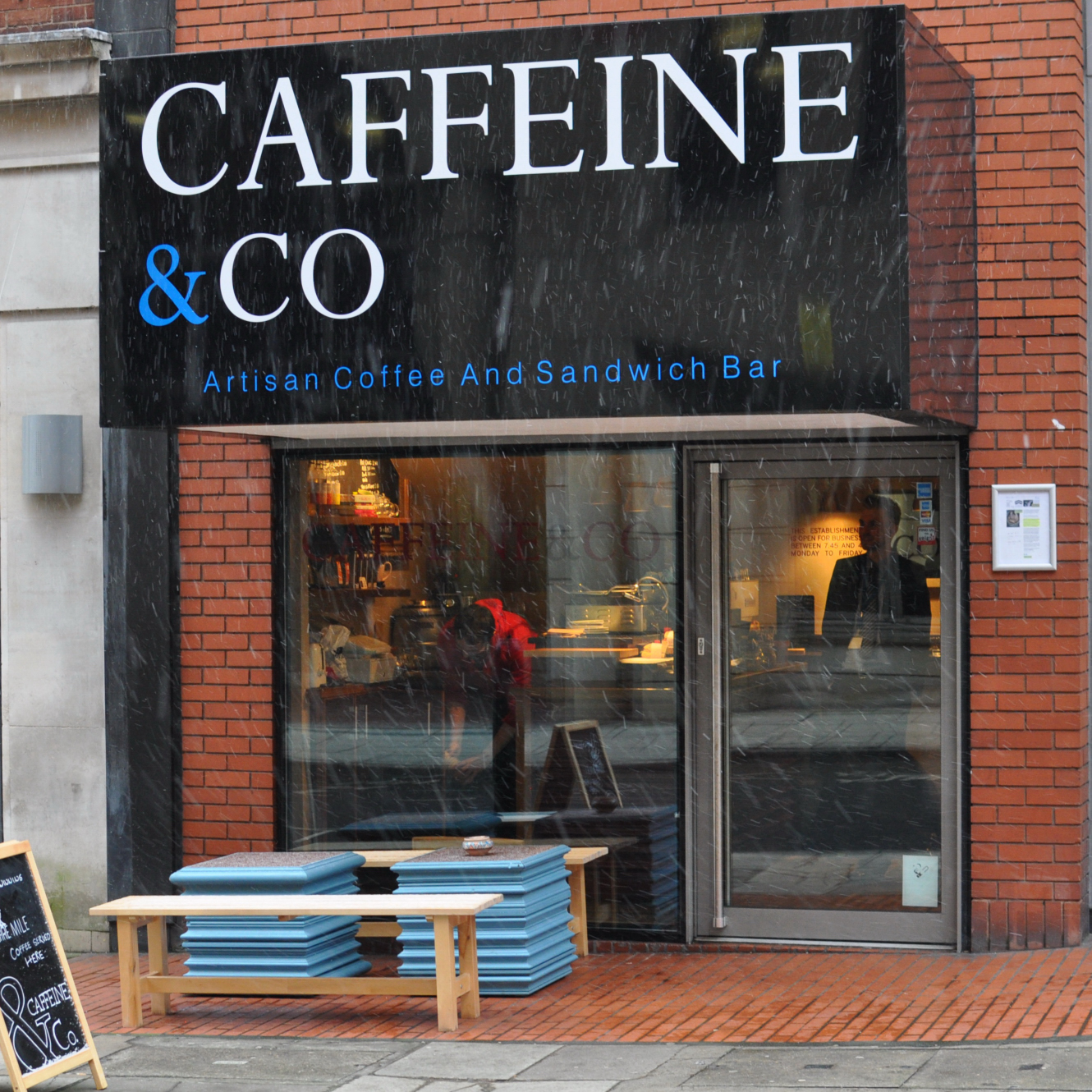 The store front of Caffeine & Co, on Manchester's St James's Square, where the most is made of what little frontage there is with a huge logo!