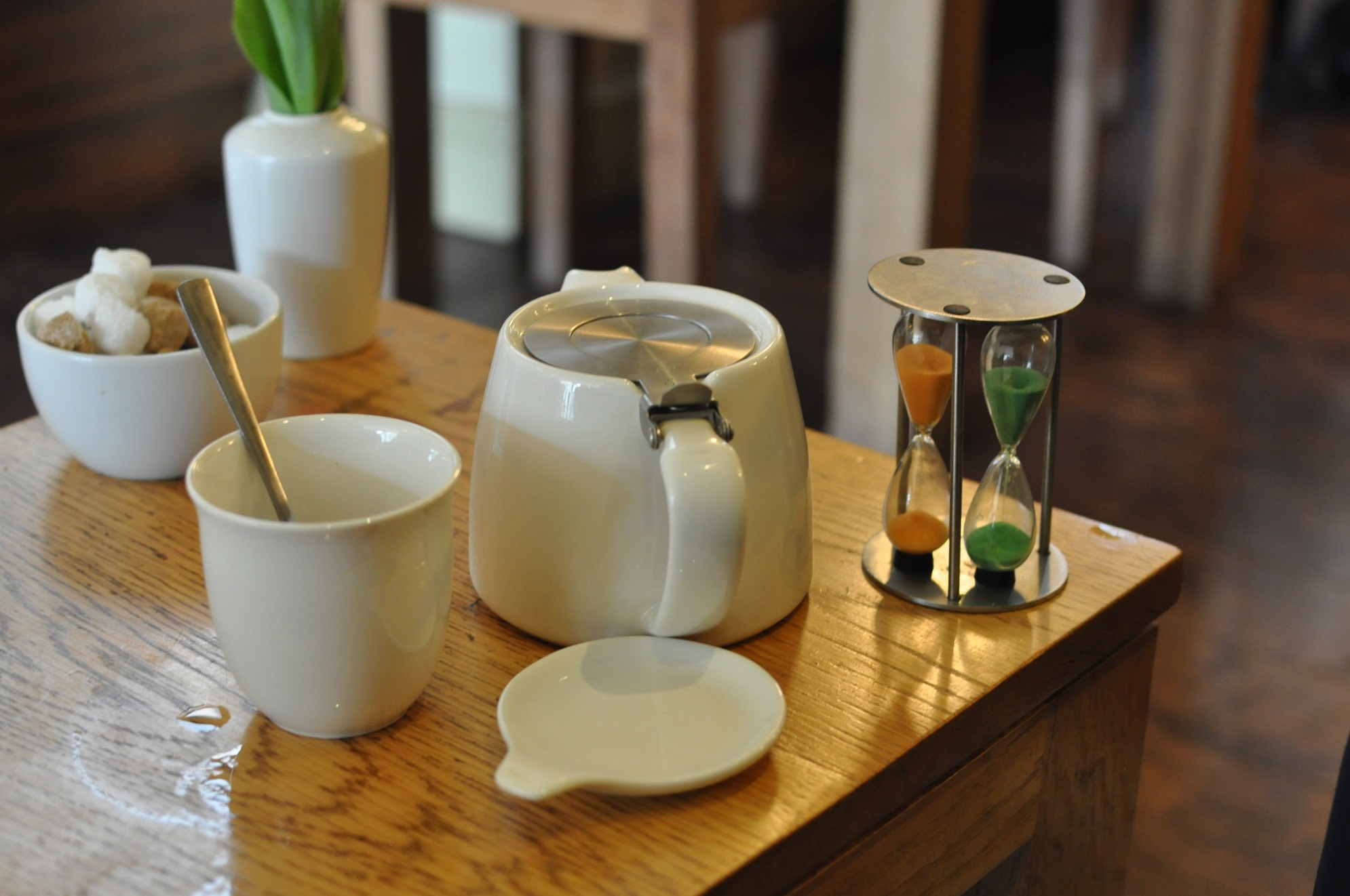 A teapot brewing at Waterloo tea with dual egg timers (one orange, one green; what tea you have determines which one you use)