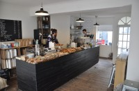 The counter at Coffee@33, burdened with sandwiches and cake, with the espresso machine at the far end.