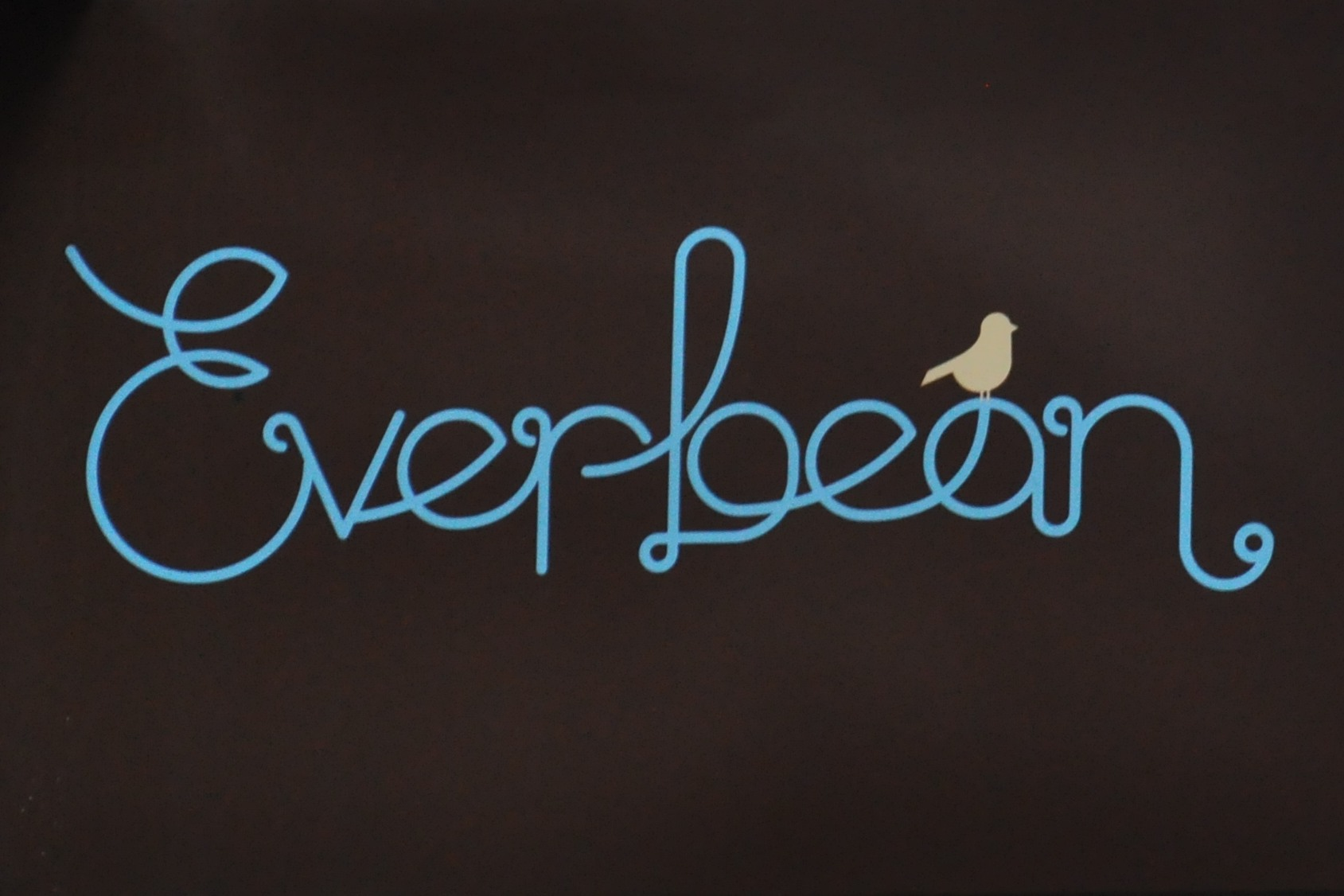 Everbean written in a cursive script, blue on brown, with the outline of a bird on the a