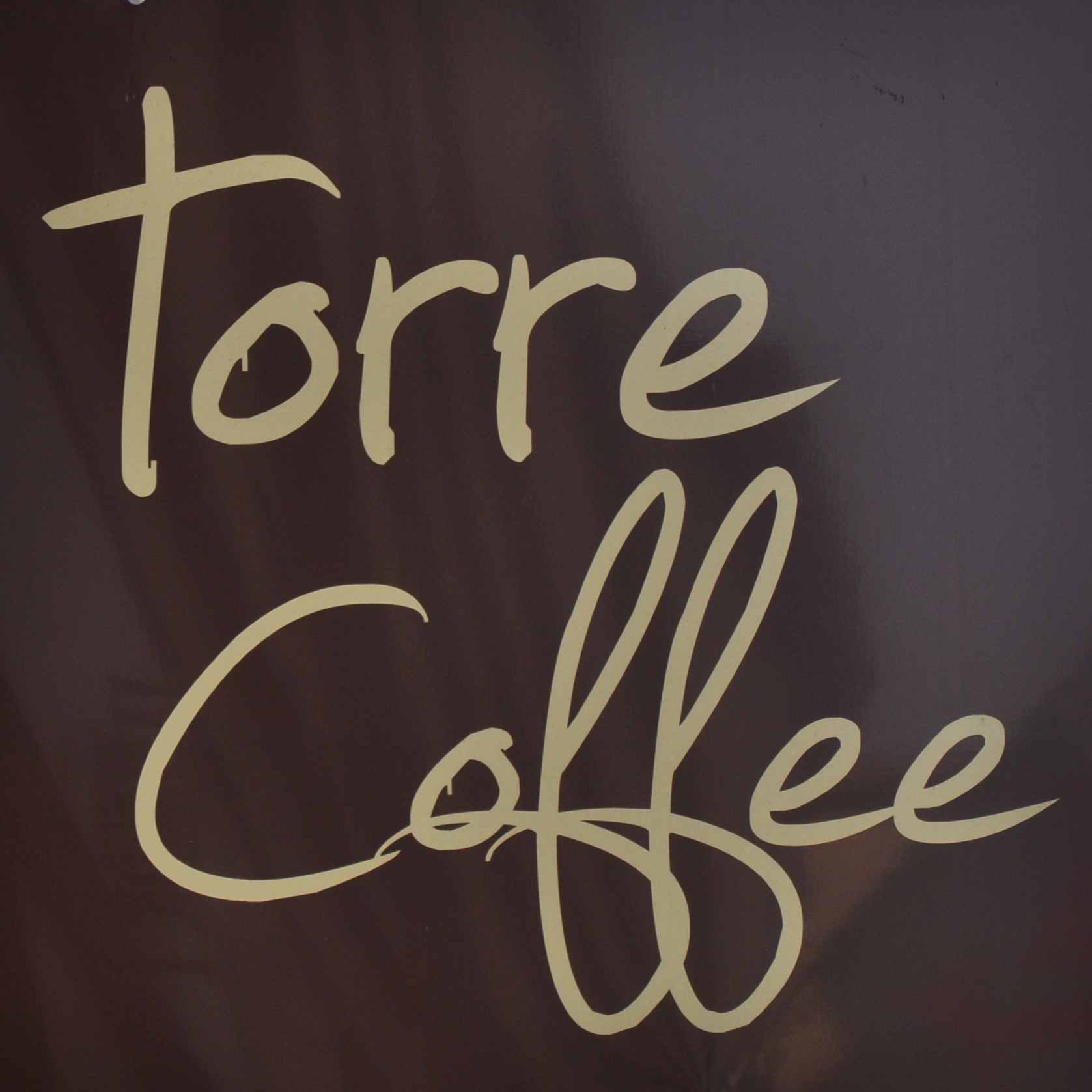 "Torre Coffee, from the sign hanging outside the shop: the words ""torre coffee"" written in a cursive script, cream on brown."