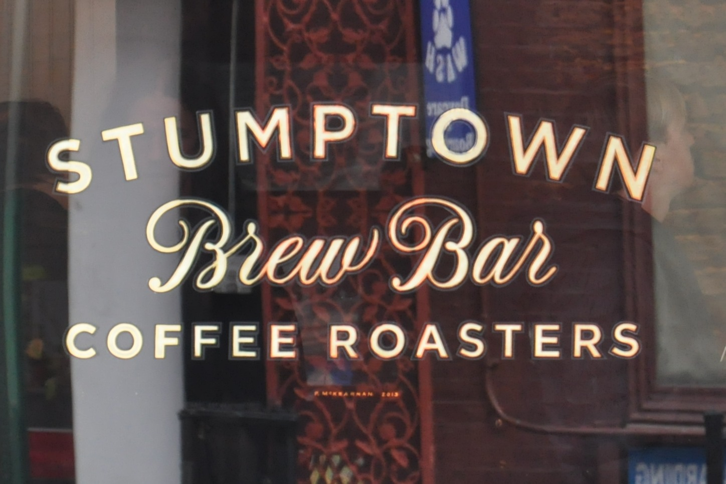 "The writing on the window of the Brew Bar part of Stumptown, W 8th St,, New York City. ""STUMPTOWN"" over ""COFFEE ROASTERS"" in capitals, with ""Brew Bar"" in cursive script in between."