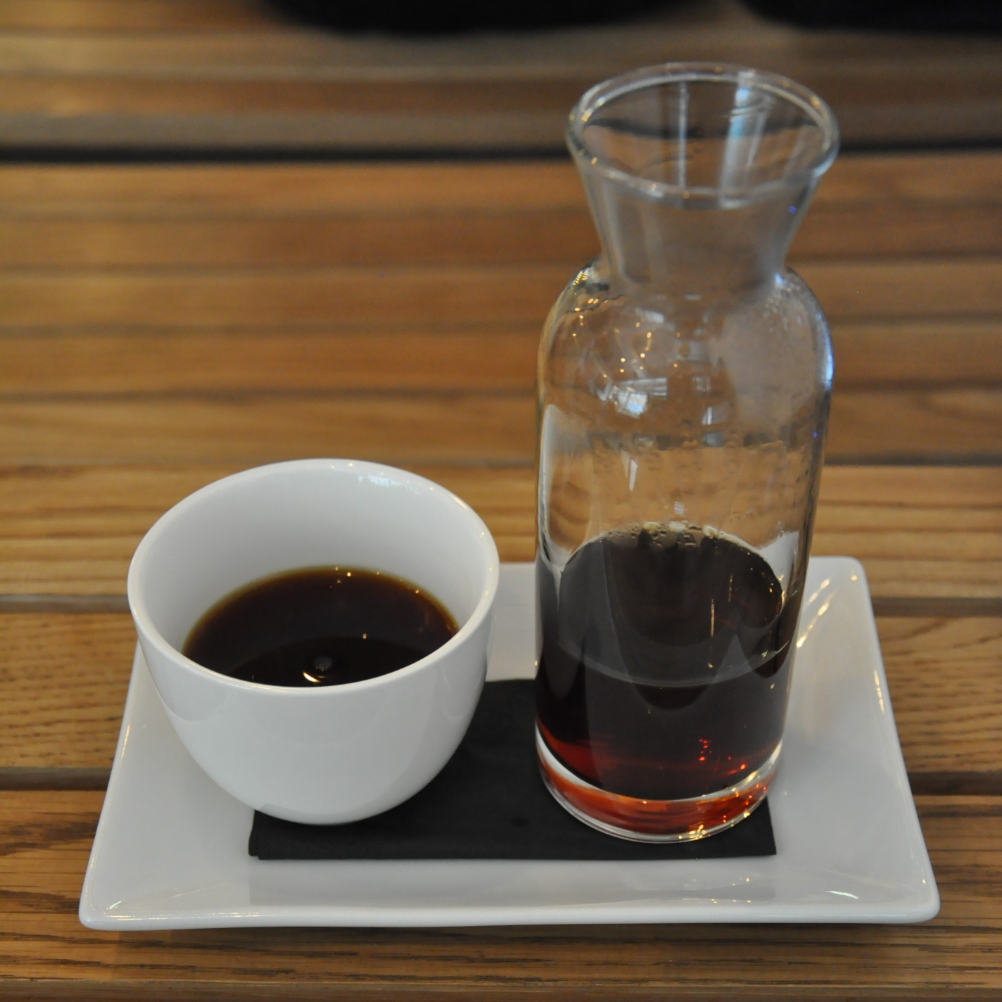 An Ethiopian Duromina from Workshop at Sharps Coffee Bar, beautifully presented in a glass carafe and a white, handless cup on a white china tray.