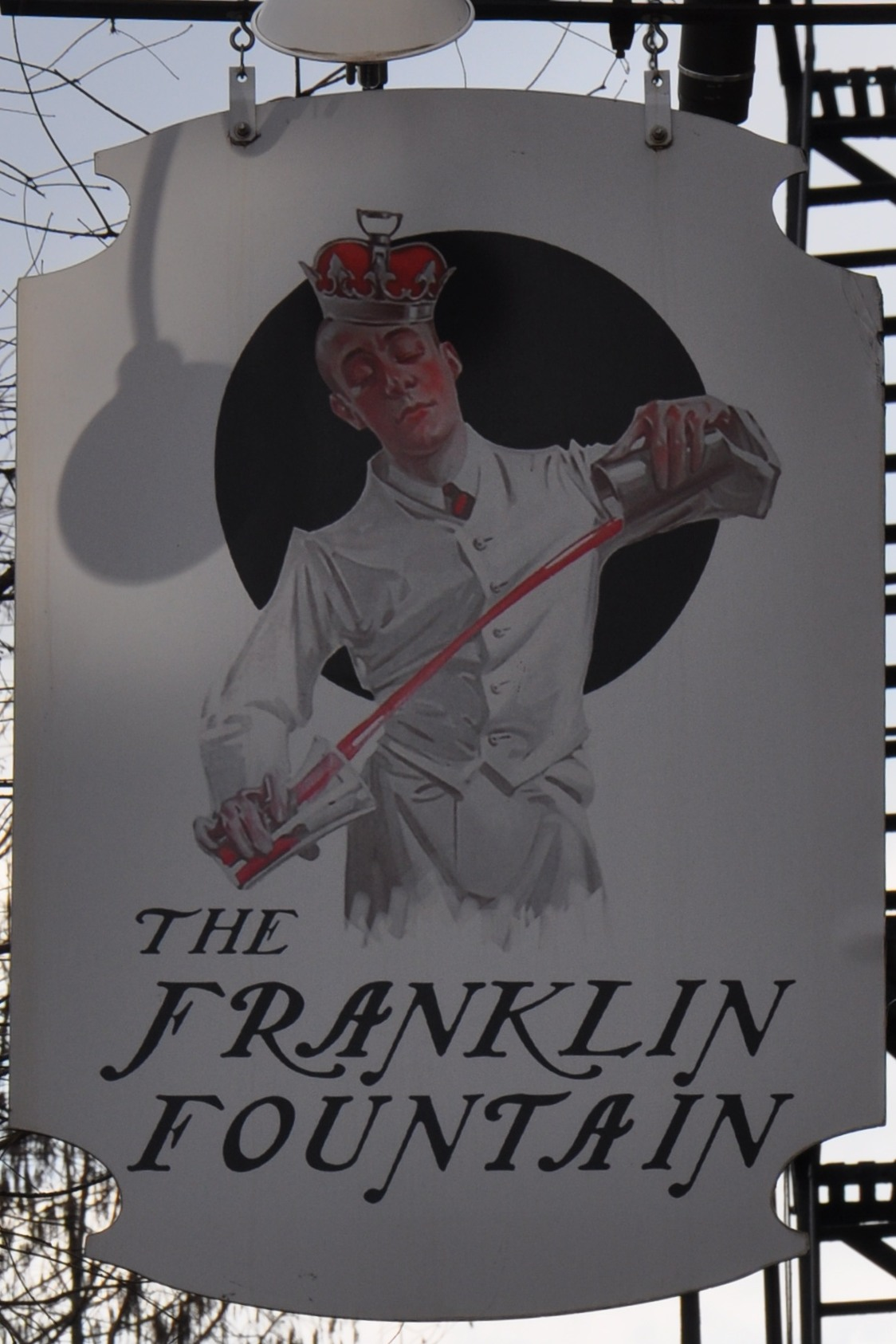 The Franklin Fountain sign, showing a man in a white uniform, mixing sodas.