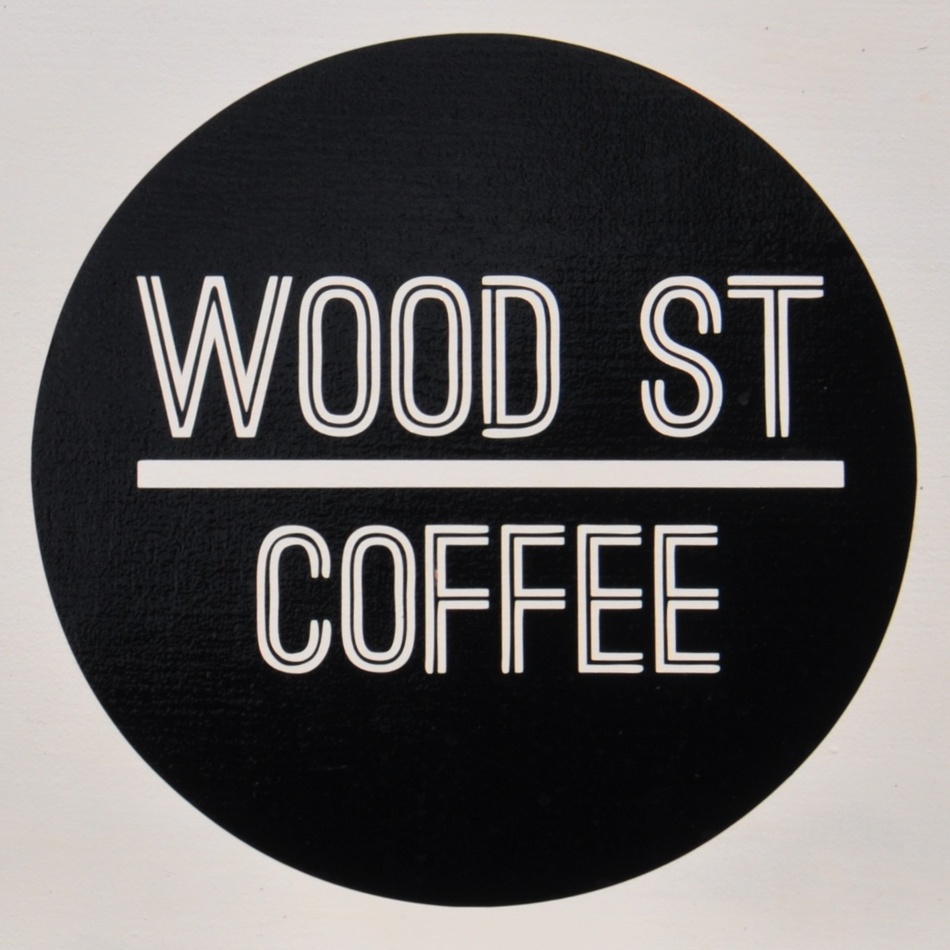"Wood Street Coffee logo, white writing on a black circle, ""Wood St"" above the line, ""Coffee below it."