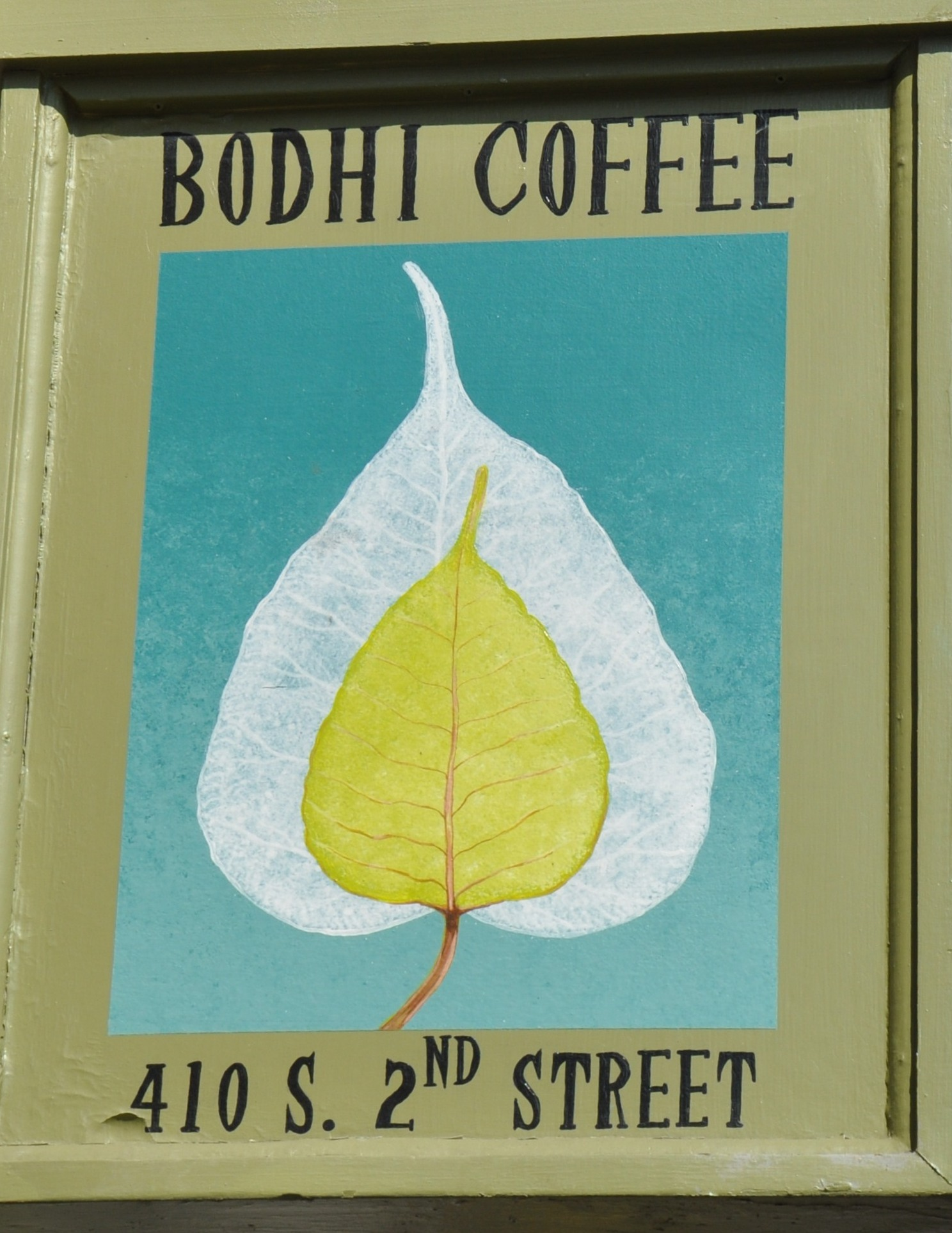 """The sign outside Bodhi Coffee. Bodhi's symbol, a leaf, topped by the words """"Bodhi Coffee"""" with the address at the bottom."""