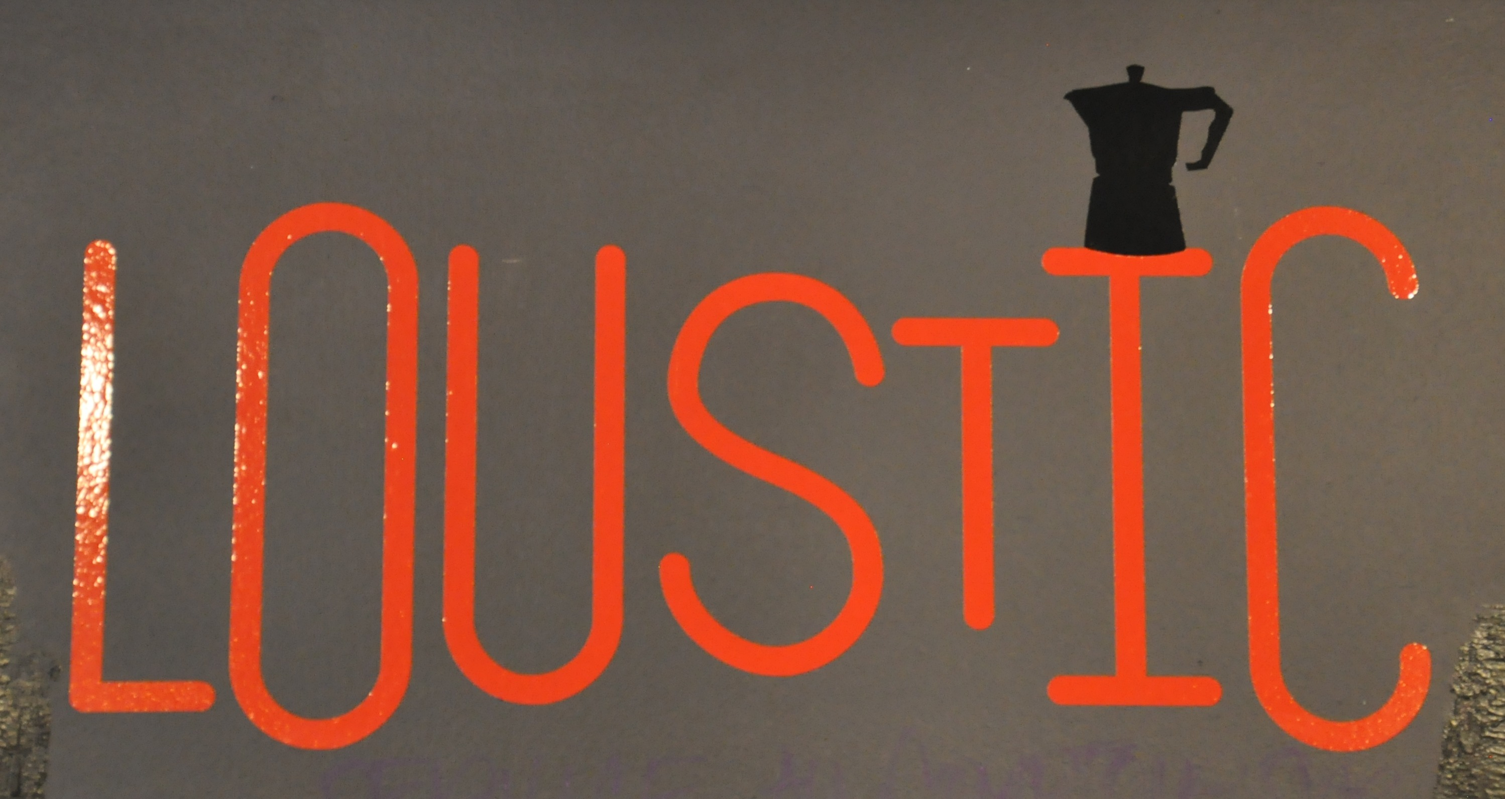 "The letters ""Loustic"" in red, with a Moka Pot balanced on top of the I."