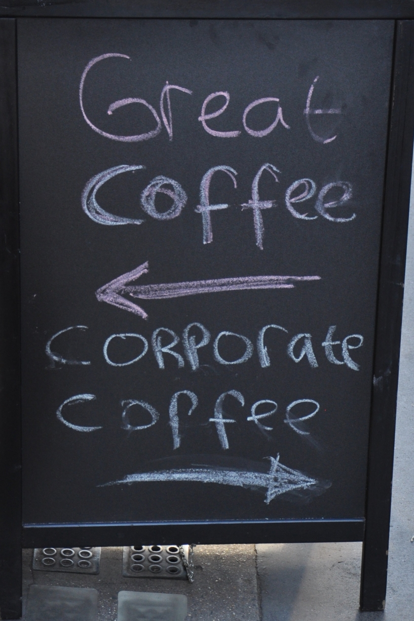 "The A-Board from The Fleet Street Press: a hand-written sign say ""Great coffee"" with an arrow pointing towards the coffee shop and another arrow, pointing the other way, labelled ""Corporate coffee""."