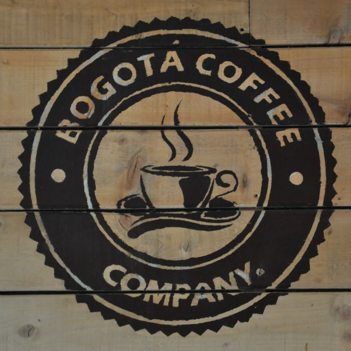 "The logo of Bogotá Coffee, painted on the wall of the coffee shop, the words ""Bogotá Coffee Company"" in a circle surrounding a steaming coffee cup."