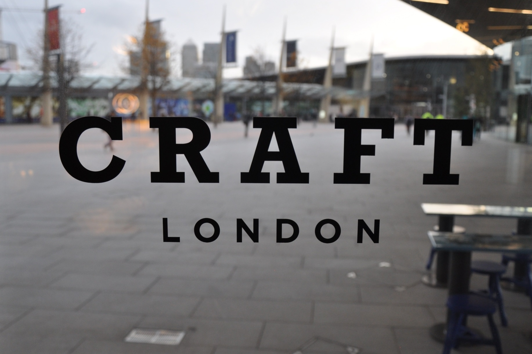 """The word """"CRAFT"""" written above the word """"LONDON"""" in the window of CRAFT London, the O2 Arena in the background."""