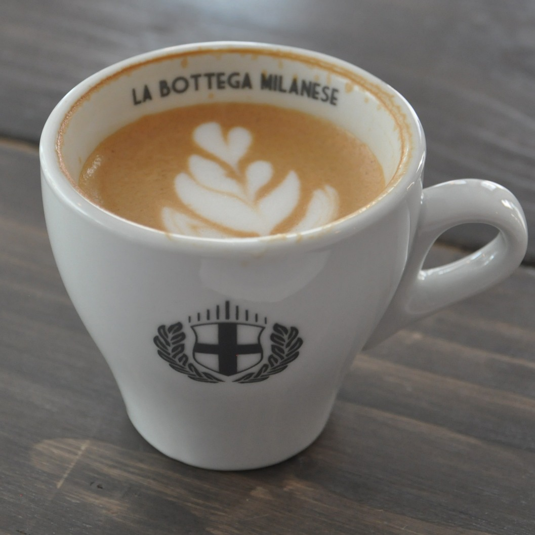 "A flat white from La Bottga Milanese in Leeds. The coffee is in a white, tulip cup with the words ""La Bottga Milanese"" written on the inside of the rim, with the cafe's logo on the front."