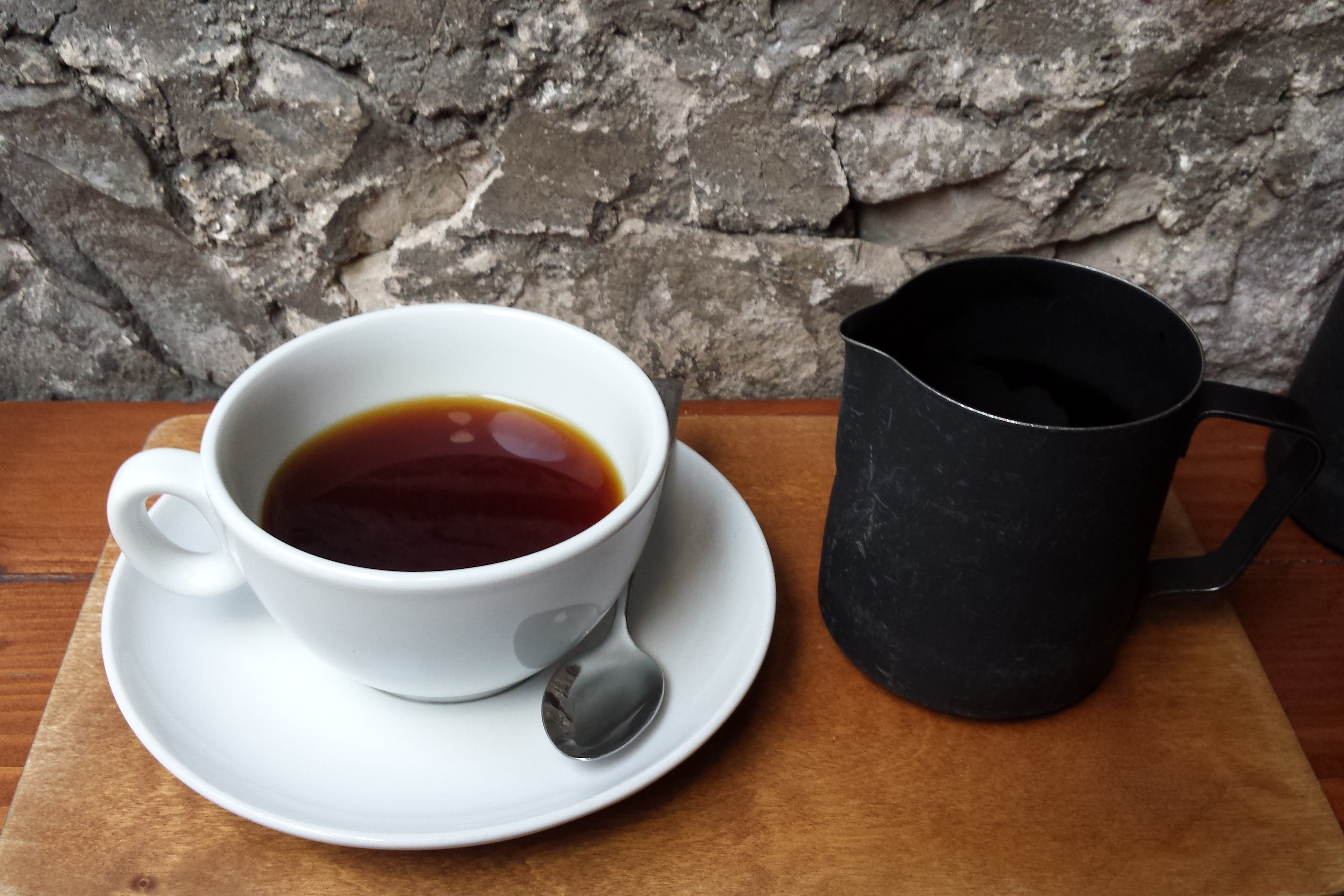 Filter coffee in a classic white cup and a black serving jug.